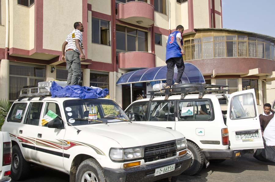 Ethiopian tour guides pack luggage on roof of Toyota Landcruisers