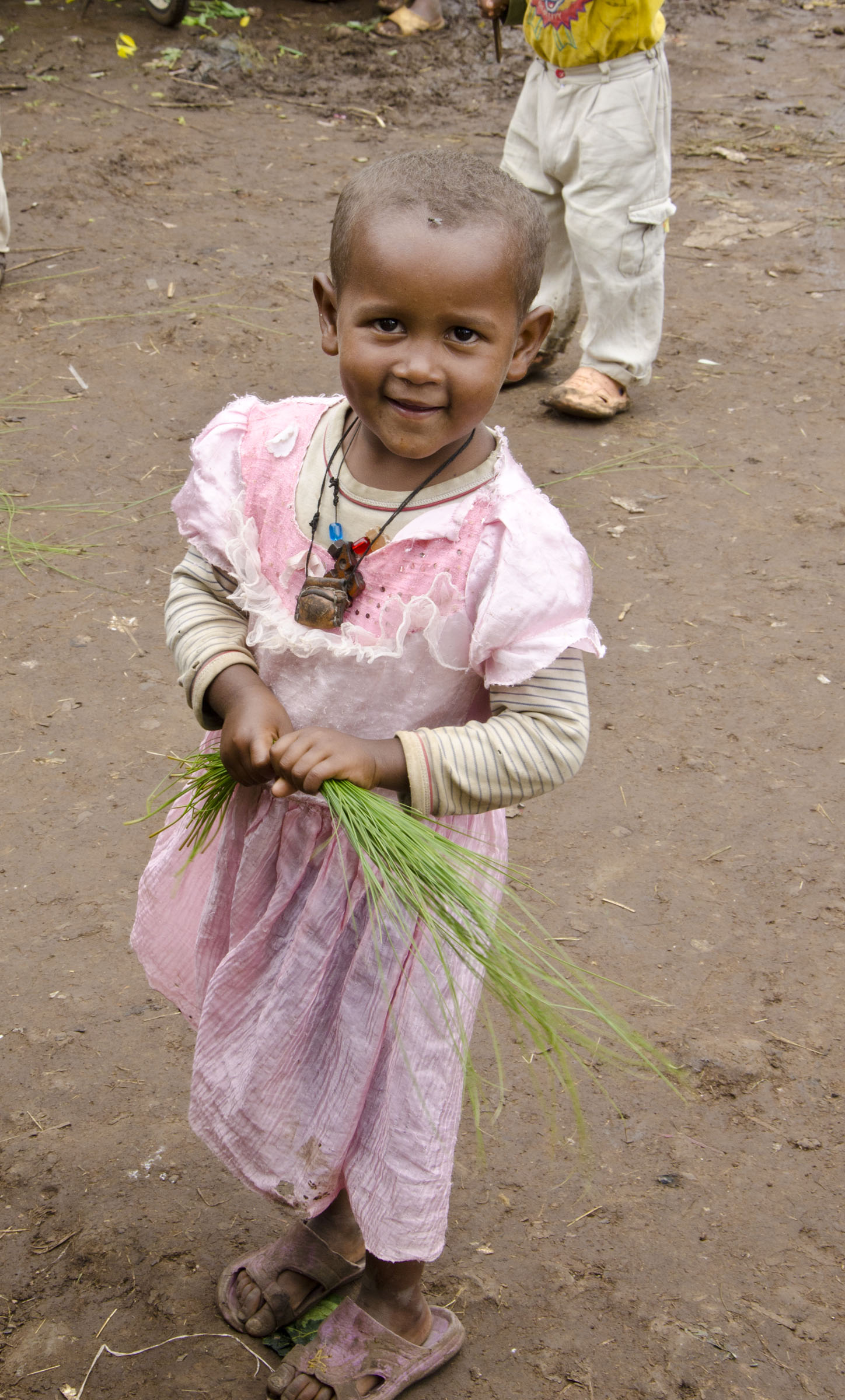 Young Ethiopian girl clutching papyrus leaves