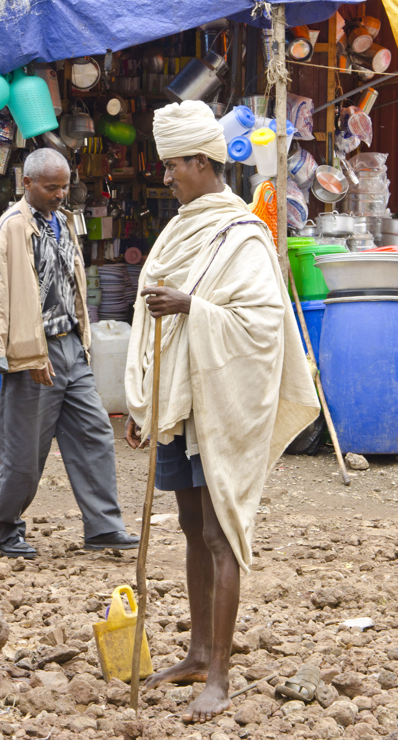 Ethiopian man with stave standing in front of market stall, Bahir Dar