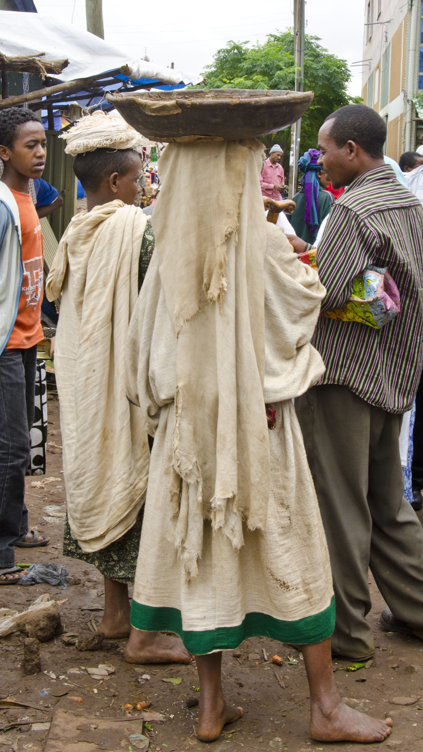 Ethiopian woman carrying wooden bowl on head