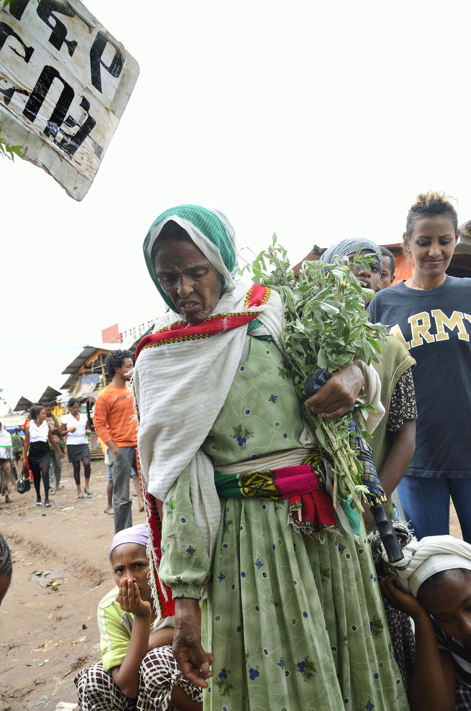 Ethiopian woman in green dress carrying herbs
